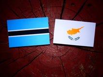 Σημαία της Μποτσουάνα με την κυπριακή σημαία σε ένα κολόβωμα δέντρων που απομονώνεται Στοκ φωτογραφία με δικαίωμα ελεύθερης χρήσης