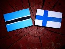 Σημαία της Μποτσουάνα με τη φινλανδική σημαία σε ένα κολόβωμα δέντρων που απομονώνεται Στοκ εικόνα με δικαίωμα ελεύθερης χρήσης