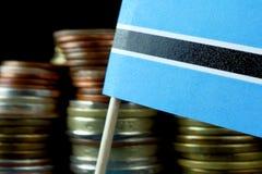 Σημαία της Μποτσουάνα που κυματίζει με το σωρό των νομισμάτων χρημάτων Στοκ Εικόνες