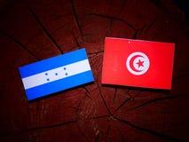 Σημαία της Ονδούρας με την τυνησιακή σημαία σε ένα κολόβωμα δέντρων που απομονώνεται Στοκ εικόνες με δικαίωμα ελεύθερης χρήσης
