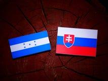 Σημαία της Ονδούρας με τη σλοβάκικη σημαία σε ένα κολόβωμα δέντρων που απομονώνεται Στοκ φωτογραφία με δικαίωμα ελεύθερης χρήσης