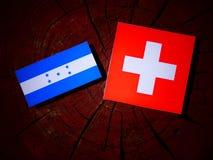 Σημαία της Ονδούρας με την ελβετική σημαία σε ένα κολόβωμα δέντρων που απομονώνεται Στοκ Εικόνες