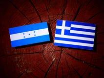 Σημαία της Ονδούρας με την ελληνική σημαία σε ένα κολόβωμα δέντρων που απομονώνεται Στοκ εικόνα με δικαίωμα ελεύθερης χρήσης