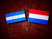 Σημαία της Ονδούρας με την ολλανδική σημαία σε ένα κολόβωμα δέντρων που απομονώνεται Στοκ φωτογραφία με δικαίωμα ελεύθερης χρήσης