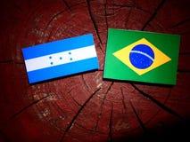 Σημαία της Ονδούρας με τη βραζιλιάνα σημαία σε ένα κολόβωμα δέντρων που απομονώνεται Στοκ εικόνες με δικαίωμα ελεύθερης χρήσης