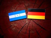 Σημαία της Ονδούρας με τη γερμανική σημαία σε ένα κολόβωμα δέντρων Στοκ Φωτογραφίες