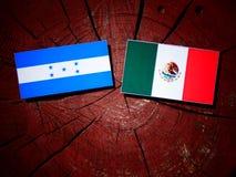 Σημαία της Ονδούρας με τη μεξικάνικη σημαία σε ένα κολόβωμα δέντρων που απομονώνεται Στοκ φωτογραφία με δικαίωμα ελεύθερης χρήσης