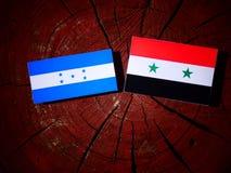 Σημαία της Ονδούρας με τη συριακή σημαία σε ένα κολόβωμα δέντρων που απομονώνεται Στοκ εικόνα με δικαίωμα ελεύθερης χρήσης