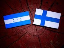 Σημαία της Ονδούρας με τη φινλανδική σημαία σε ένα κολόβωμα δέντρων που απομονώνεται Στοκ εικόνα με δικαίωμα ελεύθερης χρήσης
