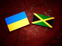 Σημαία της Ουκρανίας με την τζαμαϊκανή σημαία σε ένα κολόβωμα δέντρων Στοκ Εικόνες
