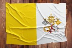 Σημαία της πόλης του Βατικανού - ιερής δείτε σε ένα ξύλινο επιτραπέζιο υπόβαθρο Ζαρωμένη τοπ άποψη σημαιών στοκ εικόνες
