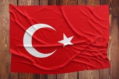 Σημαία της Τουρκίας σε ένα ξύλινο επιτραπέζιο υπόβαθρο Ζαρωμένη τουρκική τοπ άποψη σημαιών στοκ εικόνα με δικαίωμα ελεύθερης χρήσης