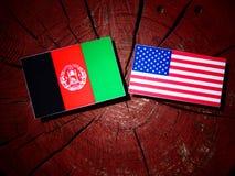 Σημαία του Αφγανιστάν με την ΑΜΕΡΙΚΑΝΙΚΗ σημαία σε ένα κολόβωμα δέντρων στοκ εικόνες