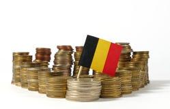 Σημαία του Βελγίου με το σωρό των νομισμάτων χρημάτων στοκ εικόνα