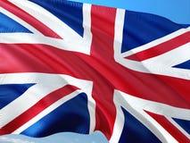 Σημαία του Ηνωμένου Βασιλείου κυματίζω στον αέρα ενάντια στο βαθύ μπλε ουρανό r στοκ εικόνες