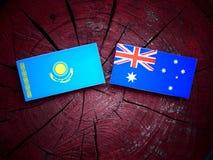 Σημαία του Καζακστάν με την αυστραλιανή σημαία σε ένα κολόβωμα δέντρων που απομονώνεται Στοκ εικόνες με δικαίωμα ελεύθερης χρήσης