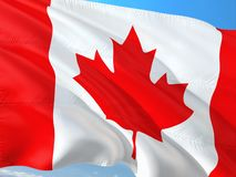 Σημαία του Καναδά που κυματίζει στον αέρα ενάντια στο βαθύ μπλε ουρανό Υψηλός - ποιοτικό ύφασμα στοκ φωτογραφία