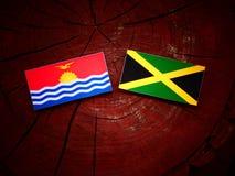Σημαία του Κιριμπάτι με την τζαμαϊκανή σημαία σε ένα κολόβωμα δέντρων Στοκ εικόνα με δικαίωμα ελεύθερης χρήσης