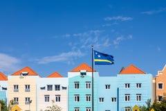Σημαία του Κουρασάο από τα μπλε κτήρια κάτω από τους μπλε ουρανούς Στοκ φωτογραφία με δικαίωμα ελεύθερης χρήσης