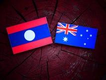 Σημαία του Λάος με την αυστραλιανή σημαία σε ένα κολόβωμα δέντρων που απομονώνεται Στοκ Φωτογραφίες