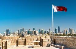 Σημαία του Μπαχρέιν με τον ορίζοντα Manama στο οχυρό του Μπαχρέιν Μια περιοχή παγκόσμιων κληρονομιών της ΟΥΝΕΣΚΟ Στοκ Εικόνες