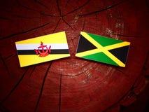Σημαία του Μπρουνέι με την τζαμαϊκανή σημαία σε ένα κολόβωμα δέντρων Στοκ Εικόνες
