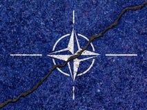 Σημαία του ΝΑΤΟ που χρωματίζεται στο ραγισμένο υπόβαθρο τοίχων/το διαιρεμένο ΝΑΤΟ concep στοκ φωτογραφίες με δικαίωμα ελεύθερης χρήσης