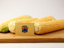 Σημαία του Νιου Τζέρσεϋ σε μια ξύλινη επιτροπή με το καλαμπόκι που απομονώνεται σε ένα λευκό Στοκ Εικόνα