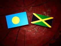 Σημαία του Παλάου με την τζαμαϊκανή σημαία σε ένα κολόβωμα δέντρων Στοκ Φωτογραφίες