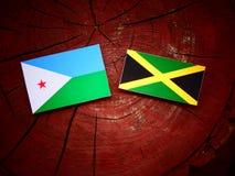 Σημαία του Τζιμπουτί με την τζαμαϊκανή σημαία σε ένα κολόβωμα δέντρων Στοκ Εικόνες