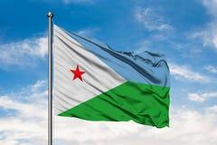 Σημαία του Τζιμπουτί που κυματίζει στον αέρα ενάντια στον άσπρο νεφελώδη μπλε ουρανό Djiboutian σημαία στοκ εικόνα