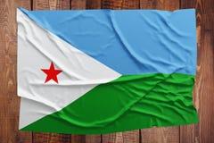 Σημαία του Τζιμπουτί σε ένα ξύλινο επιτραπέζιο υπόβαθρο Ζαρωμένη τοπ άποψη σημαιών στοκ εικόνες με δικαίωμα ελεύθερης χρήσης