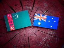 Σημαία του Τουρκμενιστάν με την αυστραλιανή σημαία σε ένα κολόβωμα δέντρων που απομονώνεται Στοκ Εικόνες