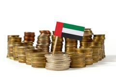 Σημαία των Ηνωμένων Αραβικών Εμιράτων με το σωρό των νομισμάτων χρημάτων στοκ εικόνα