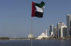 Σημαία των Ηνωμένων Αραβικών Εμιράτων στο υπόβαθρο της λιμνοθάλασσας και του Al Noor του Khalid (μουσουλμανικό τέμενος Al Noor) Σ Στοκ Εικόνες
