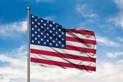 Σημαία των Ηνωμένων Πολιτειών της Αμερικής που κυματίζουν στον αέρα ενάντια στον άσπρο νεφελώδη μπλε ουρανό ΑΜΕΡΙΚΑΝΙΚΗ σημαία στοκ εικόνα με δικαίωμα ελεύθερης χρήσης