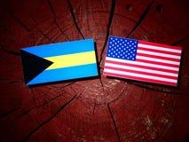 Σημαία των Μπαχαμών με την ΑΜΕΡΙΚΑΝΙΚΗ σημαία σε ένα κολόβωμα δέντρων Στοκ εικόνα με δικαίωμα ελεύθερης χρήσης