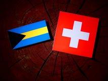 Σημαία των Μπαχαμών με την ελβετική σημαία σε ένα κολόβωμα δέντρων που απομονώνεται Στοκ Εικόνα
