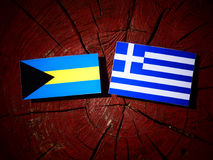 Σημαία των Μπαχαμών με την ελληνική σημαία σε ένα κολόβωμα δέντρων που απομονώνεται Στοκ εικόνες με δικαίωμα ελεύθερης χρήσης
