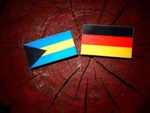 Σημαία των Μπαχαμών με τη γερμανική σημαία σε ένα κολόβωμα δέντρων Στοκ φωτογραφία με δικαίωμα ελεύθερης χρήσης