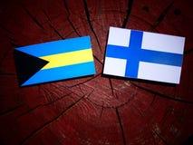 Σημαία των Μπαχαμών με τη φινλανδική σημαία σε ένα κολόβωμα δέντρων που απομονώνεται Στοκ εικόνα με δικαίωμα ελεύθερης χρήσης