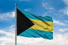 Σημαία των Μπαχαμών που κυματίζουν στον αέρα ενάντια στον άσπρο νεφελώδη μπλε ουρανό Των Μπαχάμας σημαία στοκ εικόνες