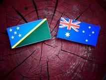 Σημαία των νήσων του Σολομώντος με την αυστραλιανή σημαία σε ένα κολόβωμα δέντρων που απομονώνεται Στοκ εικόνα με δικαίωμα ελεύθερης χρήσης