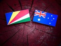 Σημαία των Σεϋχελλών με την αυστραλιανή σημαία σε ένα κολόβωμα δέντρων που απομονώνεται Στοκ Φωτογραφία