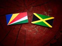 Σημαία των Σεϋχελλών με την τζαμαϊκανή σημαία σε ένα κολόβωμα δέντρων Στοκ φωτογραφία με δικαίωμα ελεύθερης χρήσης