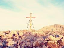 Σημαίες επίκλησης που κυματίζουν στον αέρα στο σταυρό συνόδου κορυφής Ξύλινο crucifix πάνω από το αλπικό βουνό Στοκ Φωτογραφία