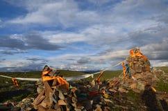 Σημαίες προσευχής γύρω από τους σωρούς πετρών καλογριών μΑ Στοκ Φωτογραφίες