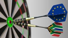 Σημαίες της Ευρωπαϊκής Ένωσης και της Νότιας Αφρικής στα βέλη που χτυπούν bullseye του στόχου Διεθνής συνεργασία ή Στοκ Εικόνα