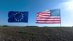 Σημαίες της Ευρωπαϊκής Ένωσης των Ηνωμένων Πολιτειών της Αμερικής και που κυματίζει μαζί στον αέρα Πραγματικός πυροβολισμός στο τ απόθεμα βίντεο