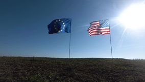 Σημαίες της Ευρωπαϊκής Ένωσης των Ηνωμένων Πολιτειών της Αμερικής και που κυματίζει μαζί στον αέρα Πραγματικός πυροβολισμός στο τ φιλμ μικρού μήκους